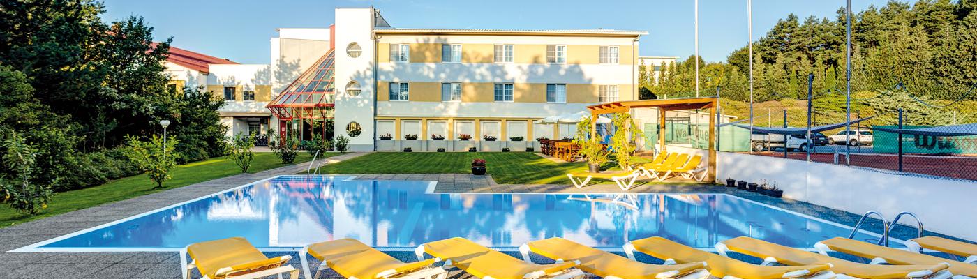 Die Aussenansicht des Sport-Hotel-Kurz, mit Pool und Liegen im Vordergrund