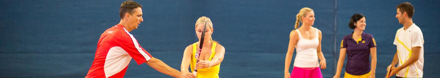 Tennisunterricht in der Tennishalle mit Tennislehrer und 4 Schülern