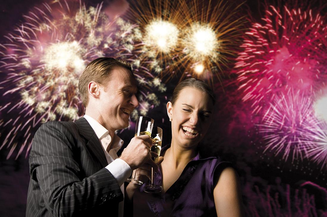 Pärchen zu Silvester mit Sektflöte in der Hand vor Feuerwerk