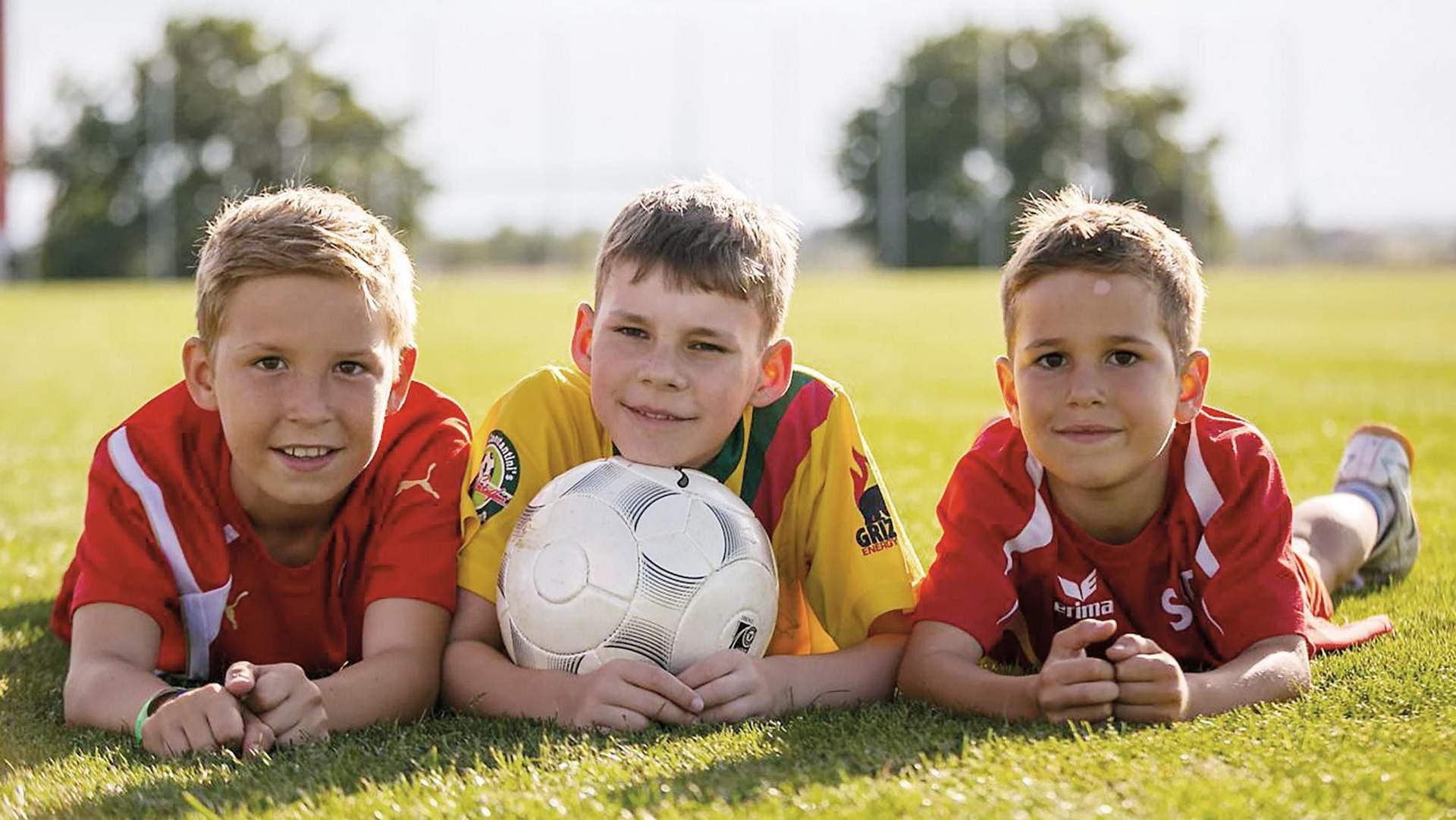 Kinder liegen auf Fußballfeld