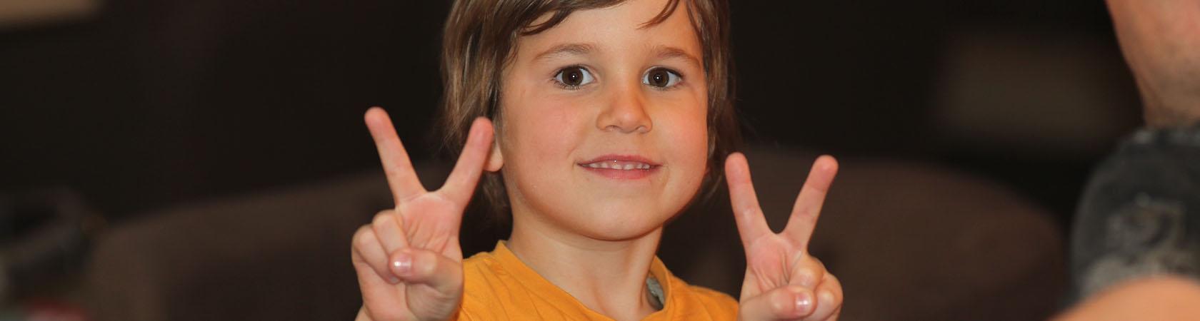Kleiner Bub zeigt mit beiden Händen das Victory-Zeichen