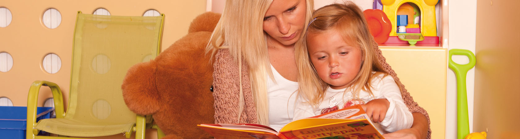 Junge Frau sitzt mit kleinem Mädchen in der Lutzi-Burg und liest ein Buch vor