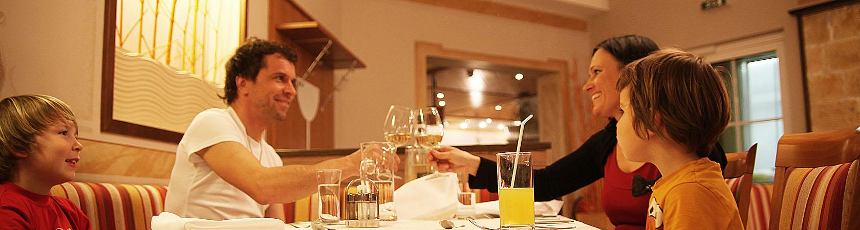 Familie sitzt beim Abendessen und prostet sich zu