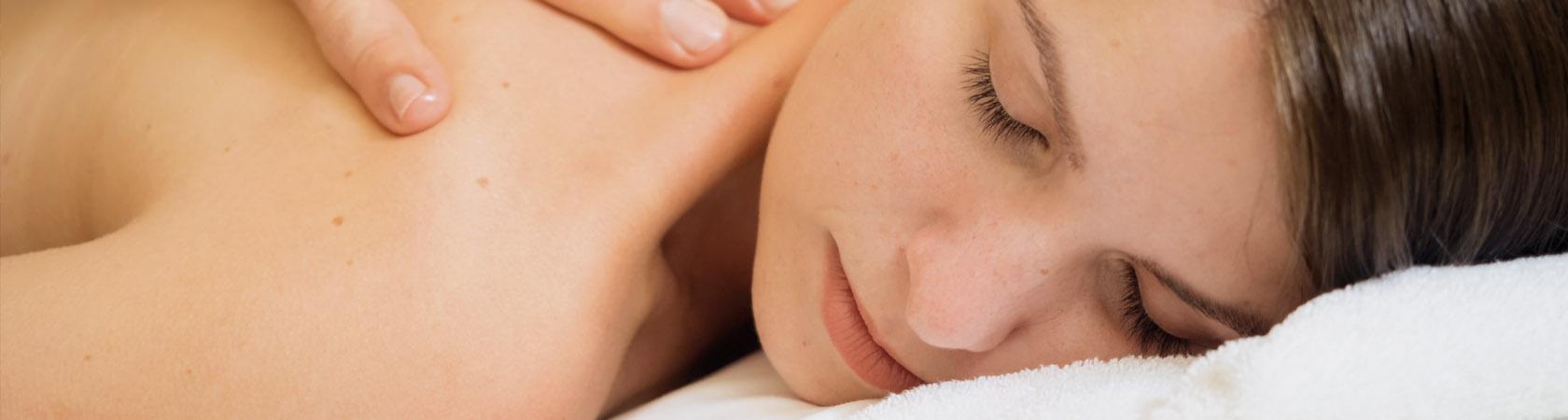 Frau genießt mit geschlossenen Augen eine Rückenmassage